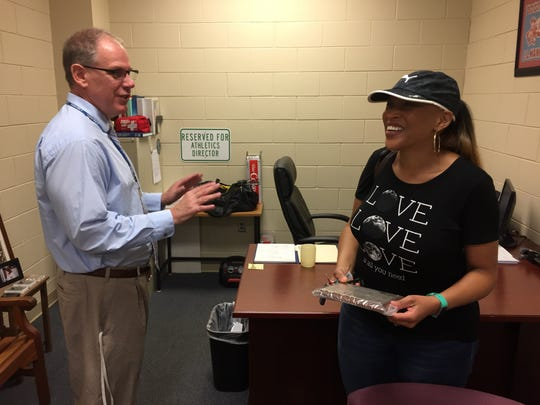 Kimberly Tate, sister of the late Eldrick Leamon, shares a laugh with J.L. Mann assistant principal Jeff Sartain in Sartain's office May 24, the day Sartain presented Tate with Leamon's basketball all-region plaque from 1994.