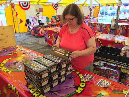 Joanna Vansickle puts out merchandise at the Community Wesleyan Church fireworks tent in Marysville.