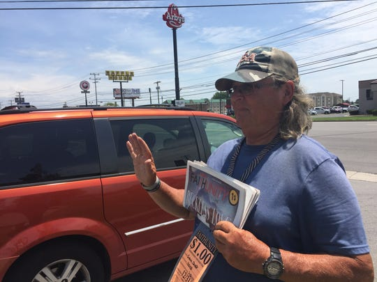 Gena Shaff waves at customers as he offers street newspapers