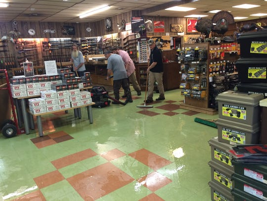 Store staff clean out flood waters from the Dickson