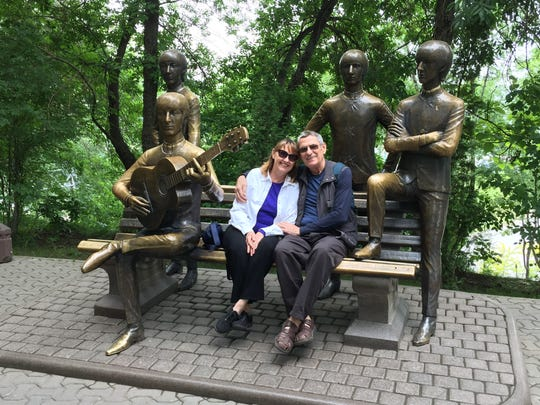 Mary and Tim Callahan pose with a bench commemorating