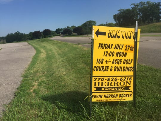 An auction sign sits with the former golf course clubhouse and parking lot in the background.