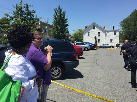 Stephanie Bell-Knight (front), of New Castle, waits to get to her car while Wilmington police talk to a barricaded subject on the roof of a home in the city's Southbridge section.