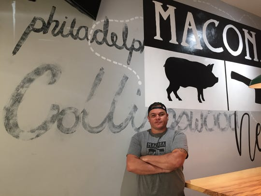 Cory Reuss, co-owner and chef of Macona BBQ, stands next to a communal table at the eatery, which is set to open this week.