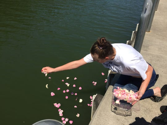 Cheyanna Decook, 20, of Gates spread pink rose petals in the Erie Canal at Henpeck Park in memory of a 6-year-old girl who drowned in the water the previous day, July 19, 2018. Decook did not know the girl.