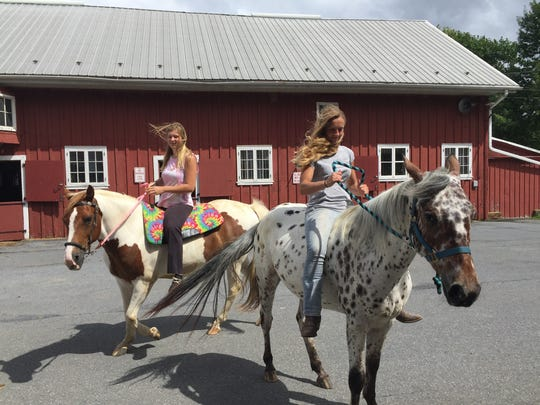Katelyn Heisey, 21, Lebanon riding her horse, Winchester, and Alicia Zeller, 19, Lebanon, on her horse, Twister, at the Quentin Riding Club July 23, 2018. Heisey and Zeller are self-service boarders at the club, meaning they take care of their own horses while boarding them at the club.  Quentin Riding Club owes $100,000 in back taxes to the county and will be put up for auction in September if the club fails to pay its debt.