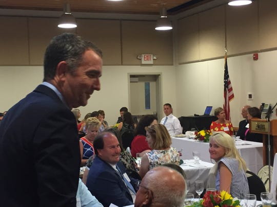 Gov. Ralph Northam chats with someone at the Eastern