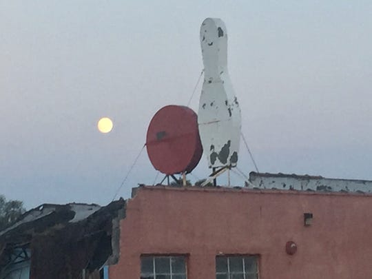 The moon glows Thursday night over a bowling ball and pin at the former Baker Lanes in Cherry Hill.