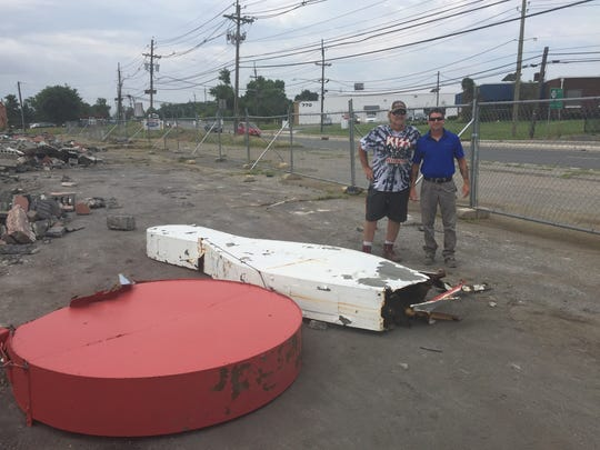 Demolition workers Jay Henderson, left, and Dan Paglaiccetti on Friday stand by iconic pin and bowl removed from the roof of former Baker Lanes bowling center in Cherry Hill.