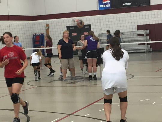 Former Newark Catholic volleyball coach Jeri Helfer encourages a middle school camper during a return drill, at the New Wave Volleyball Tuneup Clinic Sunday at the Licking County Family YMCA's Mitchell Center.