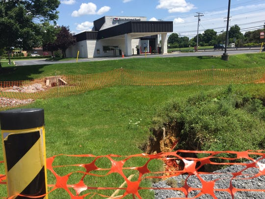 Sinkhole damage being repaired in a retention basin