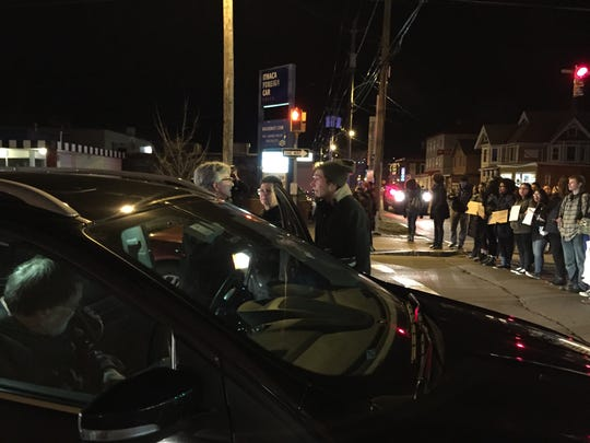 A motorist, left, and two protesters argue at a roadblock on Meadow St. in Ithaca