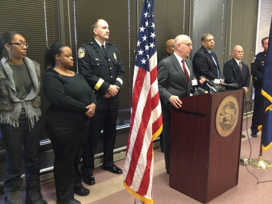 Marion County Prosecutor Terry Curry announces charges on Tuesday as relatives of slaying victim Dominique Allen look on.