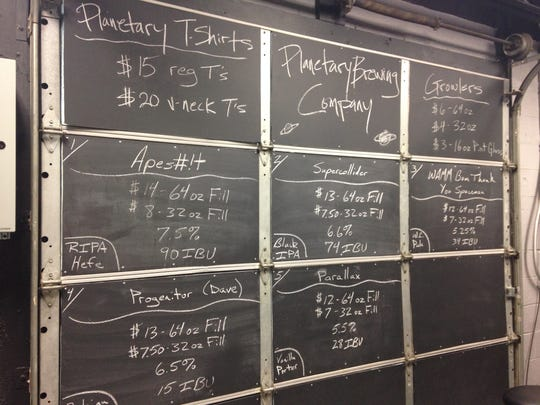 Stop 23: Available beers are listed on the back of a garage in chalk at Planetary Brewing in Greenwood.