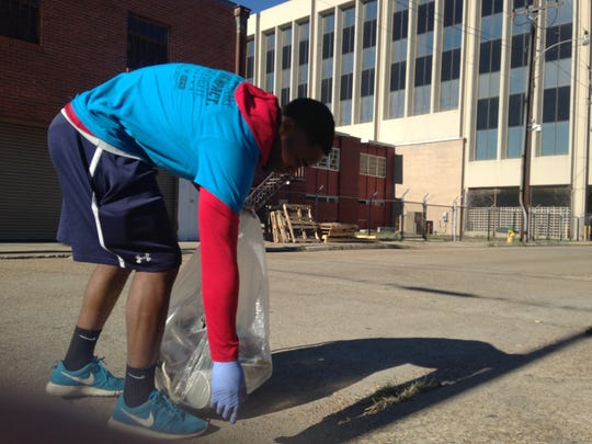 Accounting freshman Markel Perkins picks up trash from Convent Street in downtown Lafayette on Saturday for Make a Difference Day.