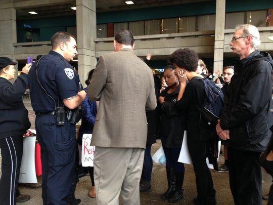 Lieutenant Aguilar of the Salem Police Department talks with protesters on Tuesday outside of the police department.