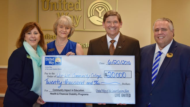 From left, United Way of the Lower Eastern Shore's executive director, Kathleen Mommé, and president, Cathie Thomas, present a $20,000 check for continuing education scholarships to Ray Hoy, president of Wor-Wic Community College and Bryan Newton.