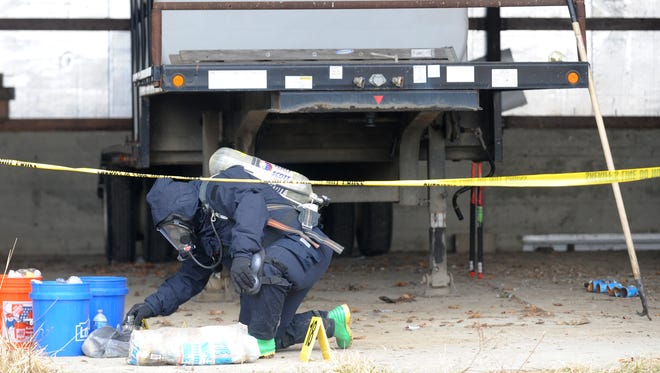 A member of the Central Ohio Drug Enforcement task force gathers evidence Tuesday at a reported meth lab in Frazeysburg. The owner of a barn off Scout Road discovered evidence of meth production and use Tuesday morning, and officials reported finding hundreds of bottles containing residue and materials used for production.