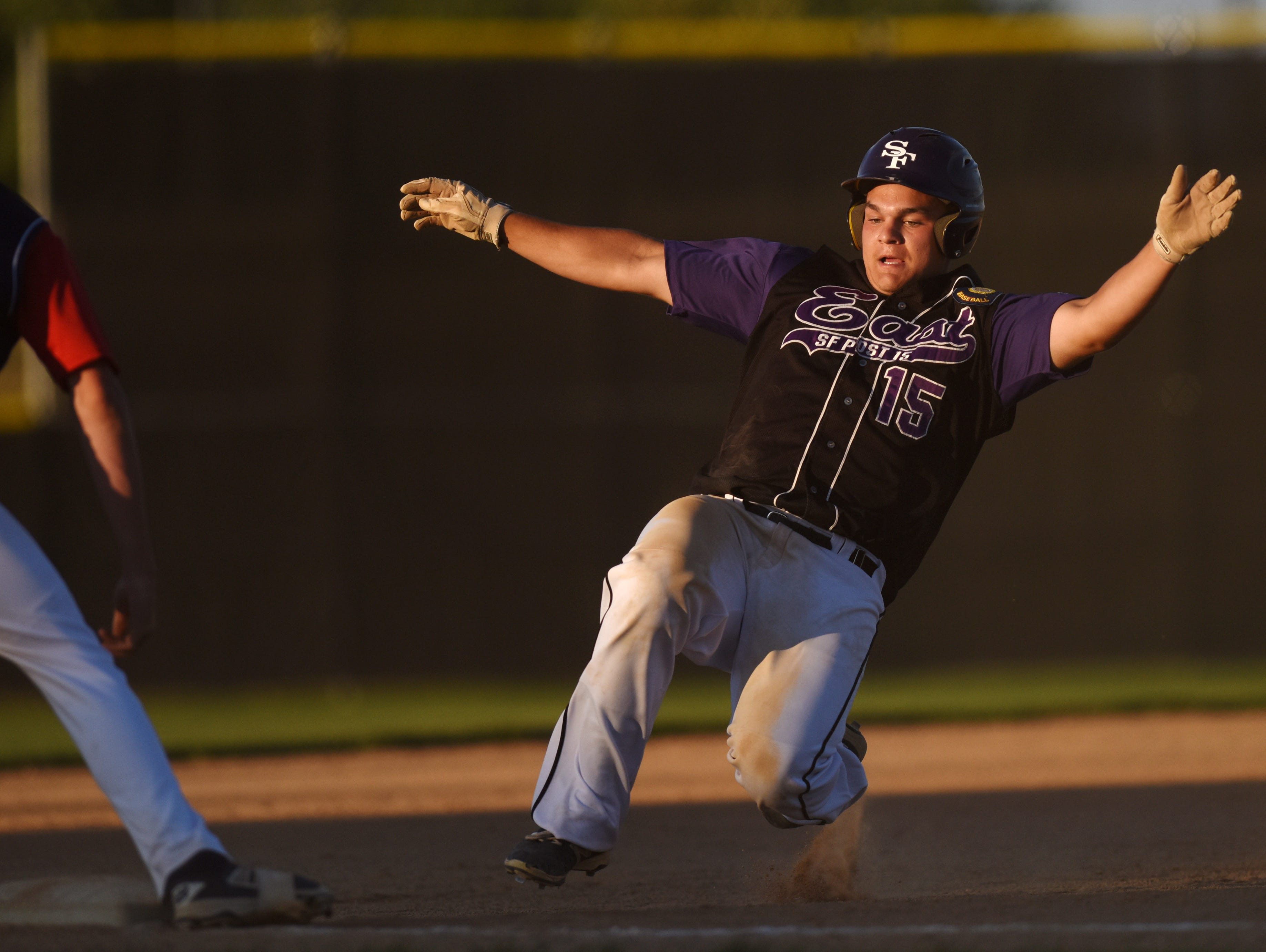 Sioux Falls Post 15 East's Corey Fichter slides safely into third while Sioux Falls Post 15 West's Alex Denevan waits on the ball during their game at Harmodon Park on Wednesday night.