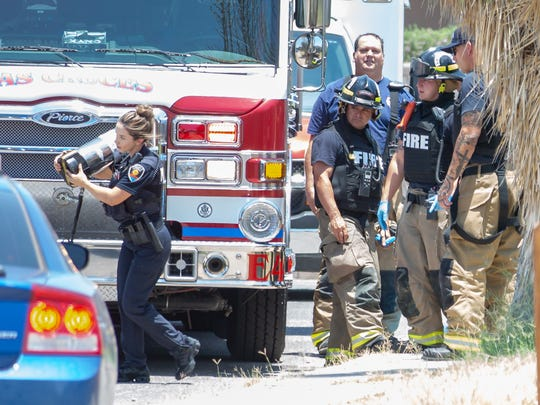 A Las Cruces police officer carries an extinguisher toward a home on the 1800 block of Boston Drive on Sunday, June 3, 2018, after police responded to a possibly burglary in progress to a home filled with smoke. Las Cruces firefighters are seen sheltering behind a firetruck wearing ballistic gear.