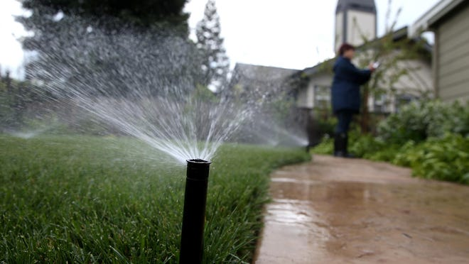East Bay Municipal Utility District (EBMUD) water conservation technician Rachel Garza inspects a sprinkler system as she performs a water conservation audit of a home on April 7, 2015 in Walnut Creek, California.