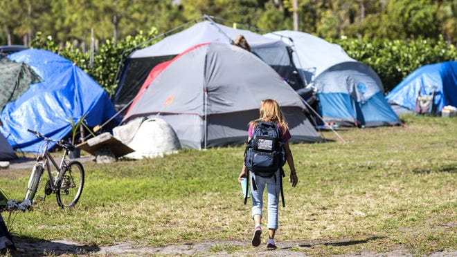 A resident walks through the homeless encampment at John Prince Park Feb. 12 while Palm Beach County workers interview homeless people.