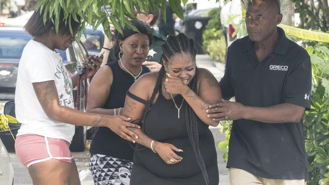 A relative of one of the victims is helped after the triple shooting in Lake Worth Beach on September 29, 2019. One man was killed and two were injured.