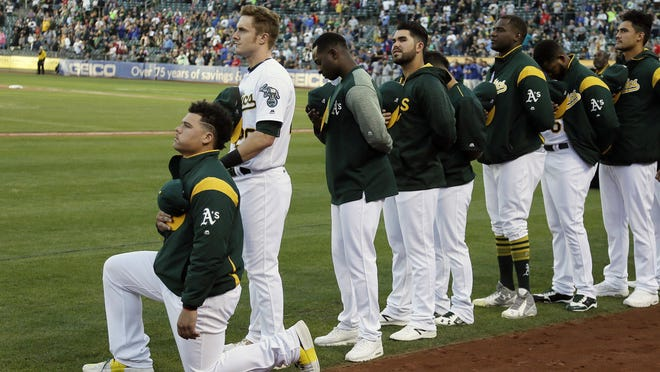 Oakland Athletics catcher Bruce Maxwell kneels during the National Anthem before the start of a baseball game against the Texas Rangers Saturday, Sept. 23, 2017, in Oakland, Calif.