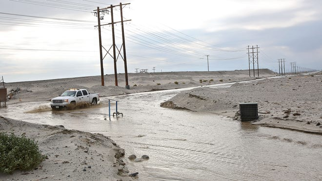 A river of water flows freely across Indian Canyon Dr. near the Amtrak train station in the large flood plain in this area during rain on December 3, 2014.