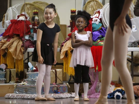 """Sujin van Hoeij, 8, left, and Corrin Hobbs, 6, smile as they watch their cast mates during rehearsal for their performance of the """"Nutcracker"""" at Tallahassee's World Ballet studio."""