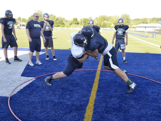 Marysville's Evan Foster and Brysen Rann try to push each other out of the circle Tyler Nunez watches a pass come to him during a drill Wednesday, Aug. 10 at Marysville High School.