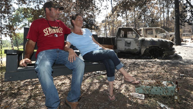 Melanie Cooper sits on a swing in her front yard with her boyfriend Bill Hattaway, in the background their vehicles and home which was burned to the ground with all of their belongings in the fire that ripped through their neighborhood on Wilderness Road in Eastpoint, Fla. The couple also lost their companion and service dog Toby in the fire.