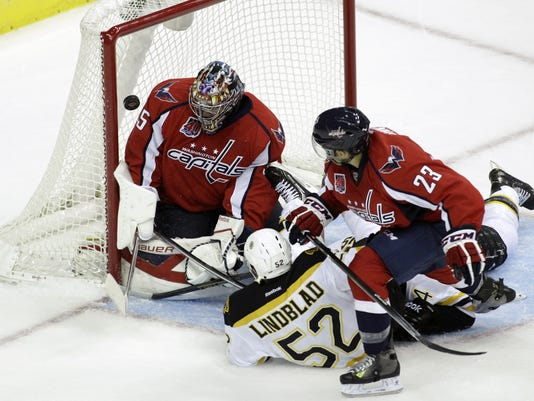 Boston Bruins' Matt Lindblad (52) scores a goal against Washington Capitals goalkeeper Justin Peters, left, as Capitals' Chris Conner (23) defends during the second period of a preseason hockey game, Friday, Sept. 26, 2014, in Washington. (AP Photo/Luis M. Alvarez)