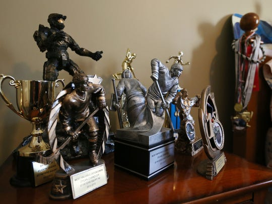 Some of Dylan Chandler's hockey and running trophies are on the night stand in his bedroom in the Chandler home.