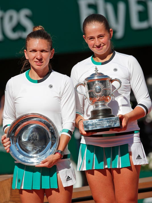 Latvia's Jelena Ostapenko, right, holds the trophy after winning the women's final match of the French Open tennis tournament against Romania's Simona Halep, left holding the runner-up trophy, at the Roland Garros stadium, in Paris, France, Saturday, June 10, 2017. (AP Photo/Christophe Ena)
