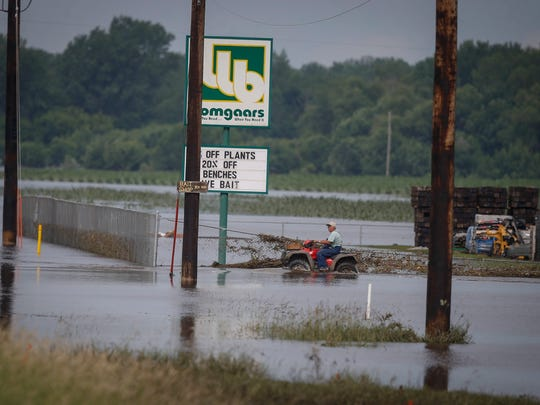 A resident of Rock Valley operates an all-terrain vehicle along a flooded roadway on Saturday, June 23, 2018, in Rock Valley.