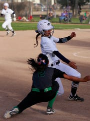 Piedra Vista's Katie Jensen tries to avoid being tagged at third base during a game against Farmington on April 22 at Ricketts Park in Farmington.