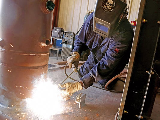 Structure welder Leonard Begaye works on a compressor Monday at San Juan Compression in Farmington.