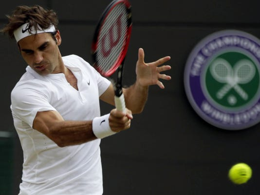 Roger Federer makes a return to Gilles Simon during their Wimbledon singles match at the All England Lawn Tennis Championships in London on Wednesday.