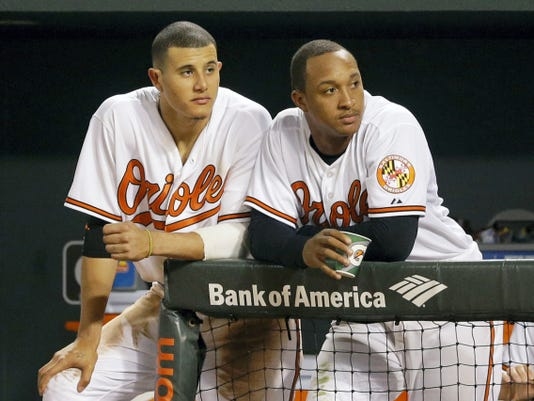 Baltimore's Manny Machado, left, and Jonathan Schoop watch from the dugout during the eighth inning of Tuesday's 11-2 loss to Tampa Bay.