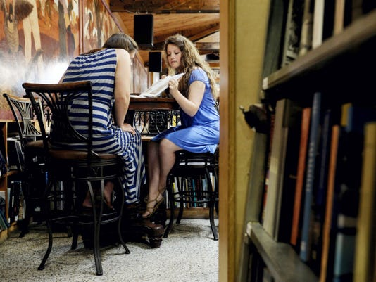 Emily Gorton, of Elizabethtown, and Lauren Busch, of Martinsville, Indiana, spend an afternoon looking at art books at Midtown Scholar Bookstore in Harrisburg on Aug. 12. The bookstore features a cafe in addition to a wide selection of contemporary books and rare editions.