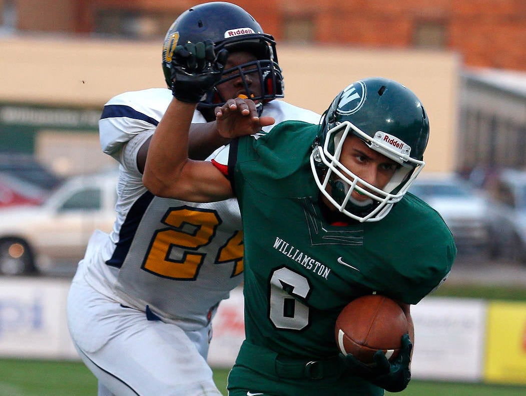Williamston's Michael Walter, right, is pushed out of bounds by Lansing Eastern's Kyangelo Robinson after catching a pass Friday, Aug. 28, 2015, in Williamston.