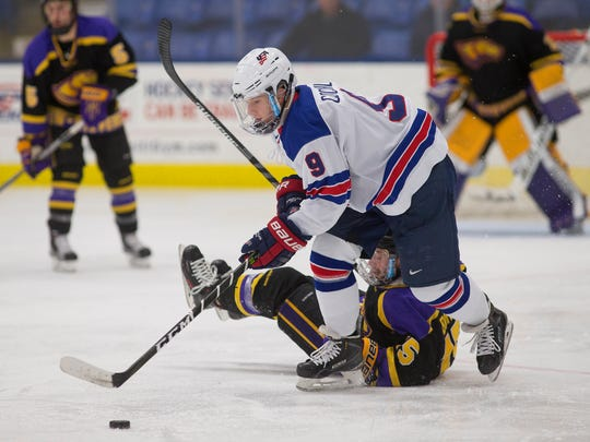 Moving away from a Wisconsin-Stevens Point player Sunday is NTDP U18 forward Logan Cockerill (No. 9) of Brighton. He scored the afternoon game's first goal in the opening period.