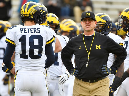 Michigan Wolverines head coach Jim Harbaugh talks with quarterback Brandon Peters (18) before a game against the Maryland Terrapins at Maryland Stadium.