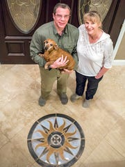 Randy and Sue Hintz stand in their Weaverville home Wednesday night. When their home was being built about six years ago, the couple came in and did all the tile and hardwood floor work in the house. Sue Hintz designed and created the mosaic in the floor at the front door.