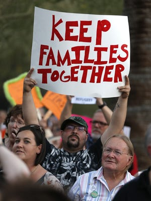 "Jimmy Gretillat holds a ""Keep Families Together"" sign outside ICE's Enforcement and Removal Operations Field Offices during a Rally for Migrants in Phoenix, Ariz. on June 17, 2018."