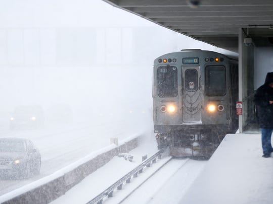 A commuter using the Chicago Transit Authority's Blue Line, braces from the wind and snow as a train heading for O'Hare International Airport approaches the Montrose Station, which runs parallel to the Kennedy Expressway, Tuesday, March 14, 2017, in Chicago. Much of the Midwest and beyond is getting snow as part of a two-day storm that forecasters say will yield between 3 to 6 inches of snow.