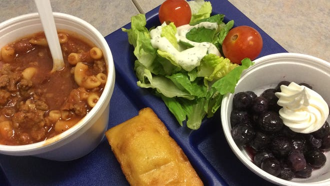 In this school lunch, homemade chili is complemented by salad, cornbread and blueberries with whipped cream.