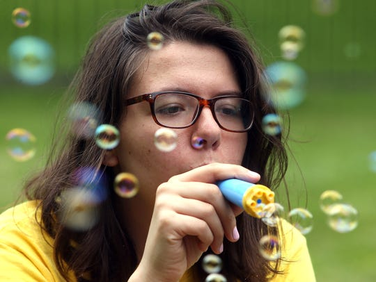 Teacher Emilia Domanowski of Chatham blows bubbles