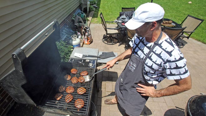 Lohud Editor Frank Scandale cooks hamburgers on the grill at his home in Glen Rock, New Jersey June 13, 2017.